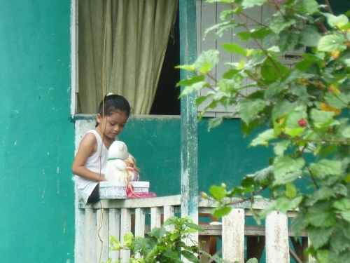 PORTRAIT OF A LITTLE GIRL ON A PORCH WITH HER TEDDY ON A SATURDAY MORNING IN BELIZE.