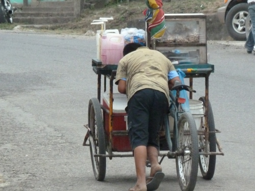 The feet will get weary in Belize: Here a 14 y.o. boy pushes his vendor cart uphill  to level ground where he can pedal it.