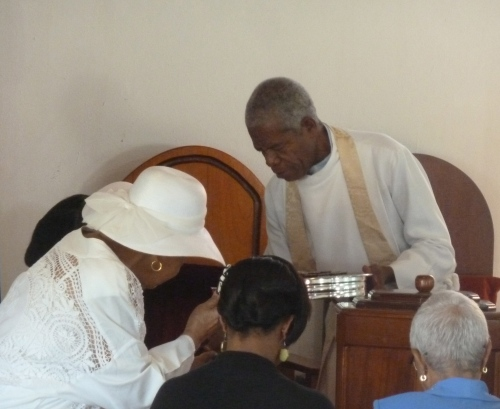The Rev. Angus Jaime serving communion to his flock at First Methodist Church, Belmopan, Belize. He also serves the First Methodist Church in Hattiesburg, a 45-minute or so drive down the road.