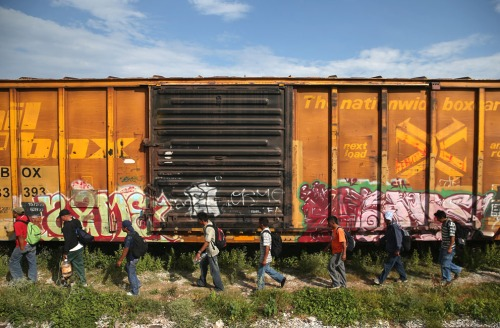 Immigrants arrive for a rest stop after a 15 hour ride atop a freight train headed north in Ixtepec, Mexico, on August 4, 2013. (John Moore/Getty Images)