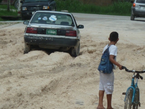 Meanwhile, back in Belize--a nation under water tonight--it's wet and, in places, seriously muddy. And he went down THAT street without 4-Wheel Drive? (4-Wheel Drive not included on Belizean bicycles.)