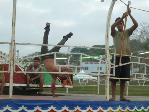 Another creepy crawler: a carny walking on his hands while his buddy works.