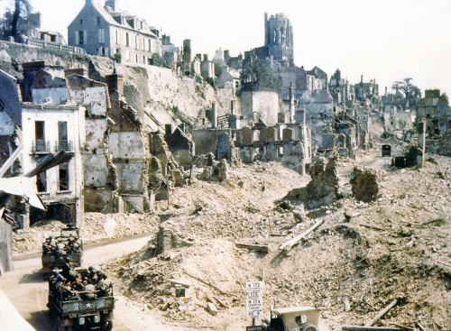 Two U. S. Army trucks and two American jeeps are driving through the ruins of Saint-Lo in August of 1944. The town was almost totally destroyed by 2,000 Allied bombers when they attacked German troops stationed there during Operation Overlord Normandy in June.  (Photo by Galerie Bilderwelt/Getty Images)