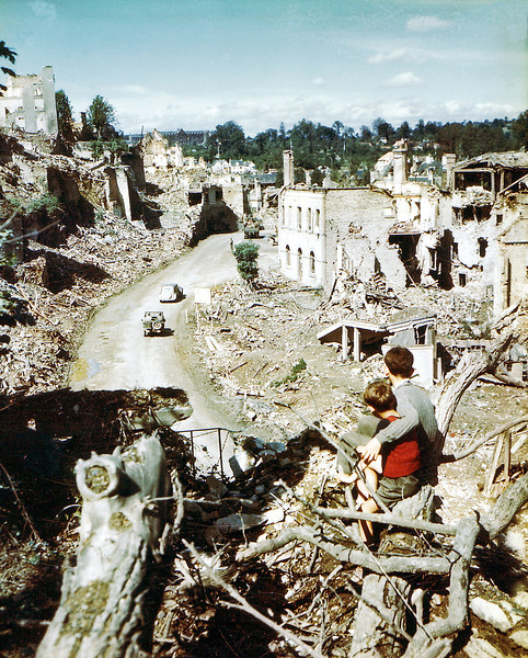 Two children watch an American Army jeep driving through the ruins of Saint-Lo in August of 1944. The town was almost totally destroyed by 2,000 Allied bombers when they attacked German troops stationed there during Operation Overlord Normandy in June.  (Photo by Galerie Bilderwelt/Getty Images)