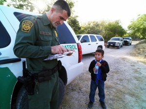Patrol agent reads the birth certificate of Alejandro, 8 -- the only thing he brought with him as he and others crossed the Rio Grande near McAllen, Texas, June 18, 2014. More than 52,000 minors traveling without parents have been caught crossing the border illegally since October -- many, like Alejandro, hoping to join parents or close relatives already here. (Jennifer Whitney/The New York Times)