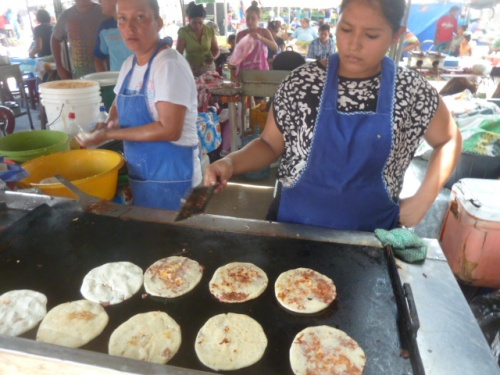 Pupusas, a native El Salvador dish popular throughout Central America. It's corn meal pancakes stuffed with meat, cheese and beans or some combination thereof, then fried. I get some at market every Saturday and try to eat reasonably healthy meals the rest of the day to offset the damage.