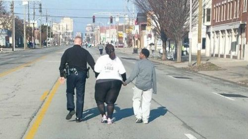 A (white)  Louisville police lieutenant took the hand of a (black) racer and helped her across the finish line of a race in Kentucky. This is evidence that Americans down on Main Street are still pretty good peeps.