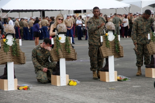 Mourners pause at crosses representing the 12 Marines who died in helicopter crashes Jan. 14 in Hawai. The crosses were adorned with flight gear, boots and Hawiian leis during a memorial Friday at Marine Corps Base Hawaii. WYATT OLSON/STARS AND STRIPES